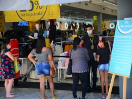 Abertura; Funcionária aplica álcool em gel mão de consumidora na entrada da loja de videogames (Foto: Divulgação/PMC)