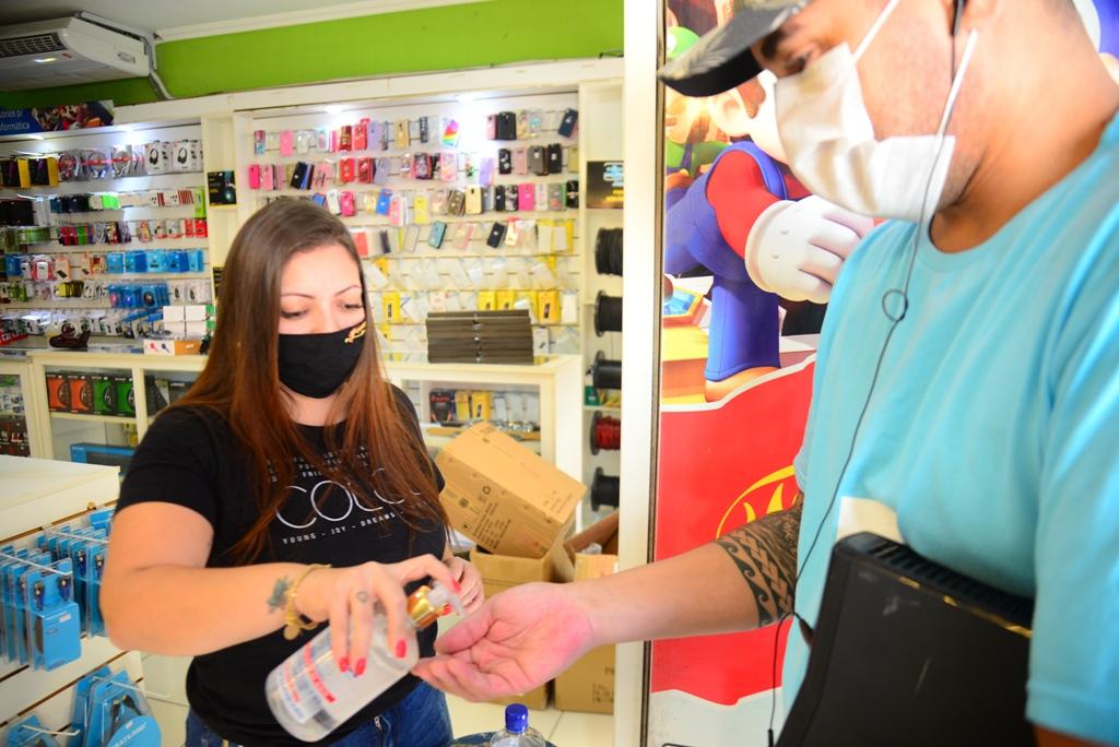 Funcionária aplica álcool em gel mão de consumidora na entrada da loja de videogames (Foto: Divulgação/PMC)